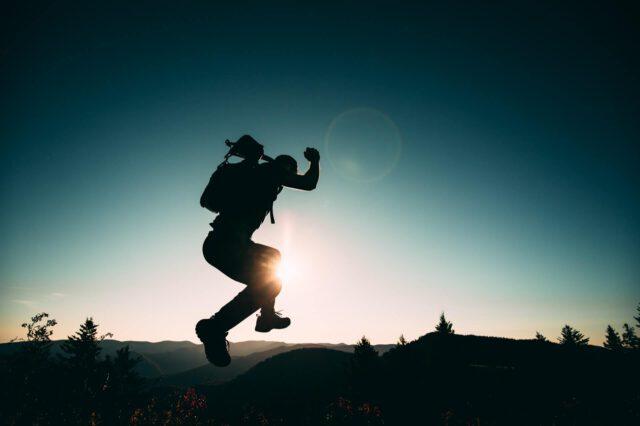 Ein Mann macht einen begeisterten Luftsprung in der Abenddämmerung