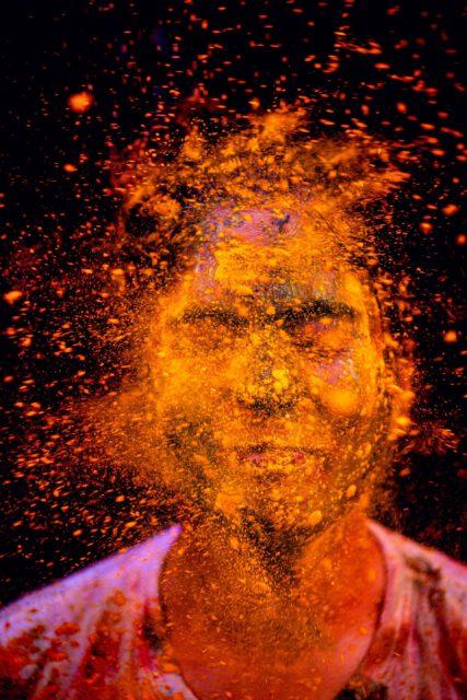 Kopf, der mit orangefarbenem Farbpuder beworfen wurde