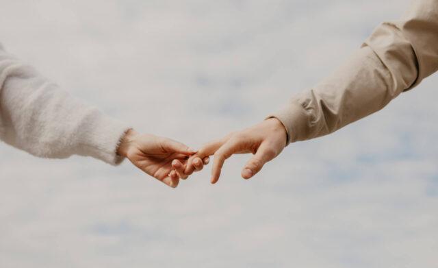 Mann und Frau berühren sich an den Fingerspitzen