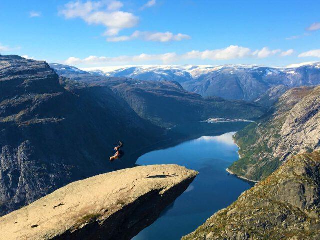 Eine Person auf einem Felsvorsprung macht einen Salto in schwindelerregender Höhe über einer weiten Berg- und Seenlandschaft