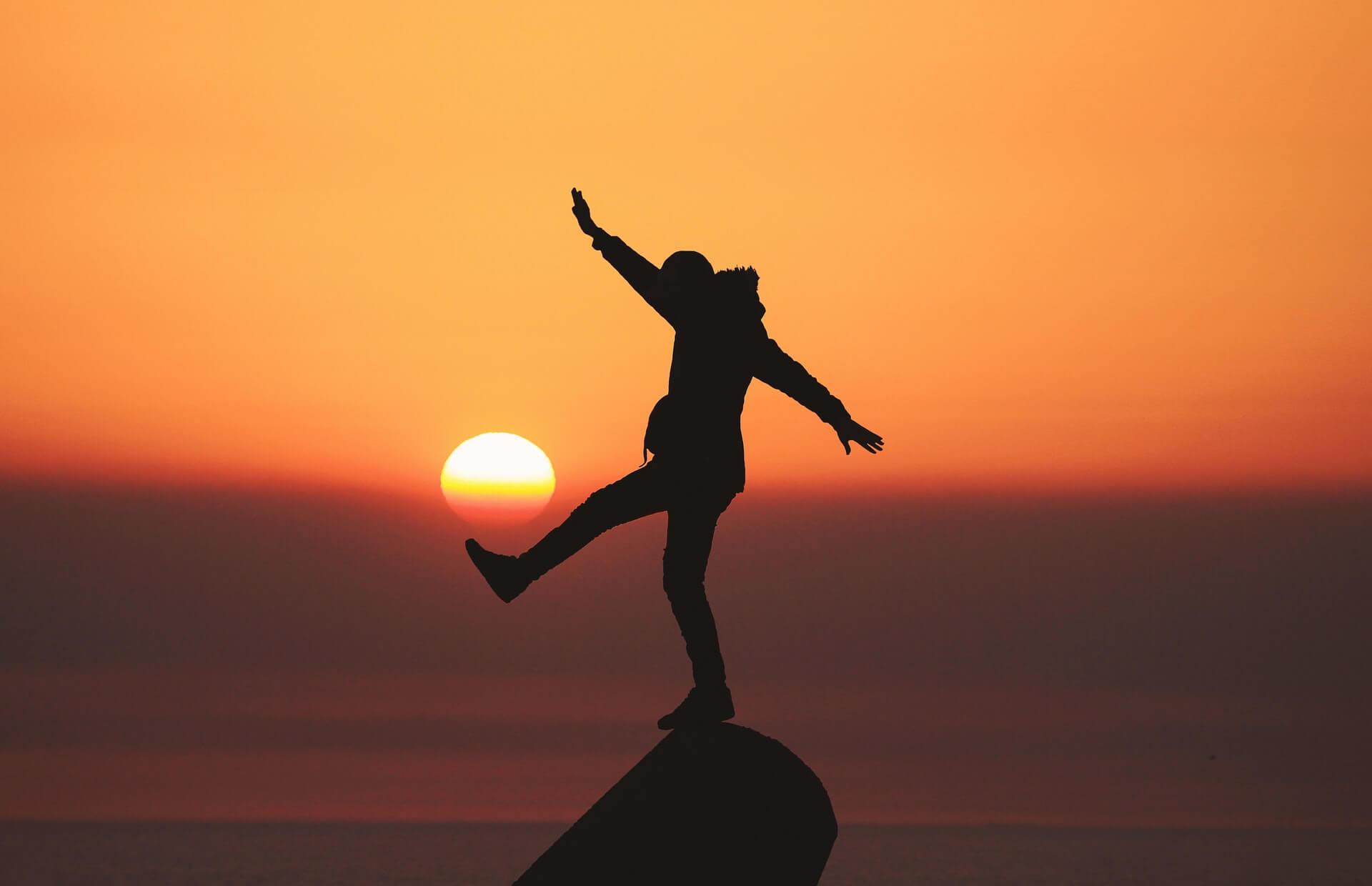 In der roten Abenddämmerung steht einbeinig eine Person auf einem Felsen und kickt die untergehende Sonne mit dem anderen Fuß