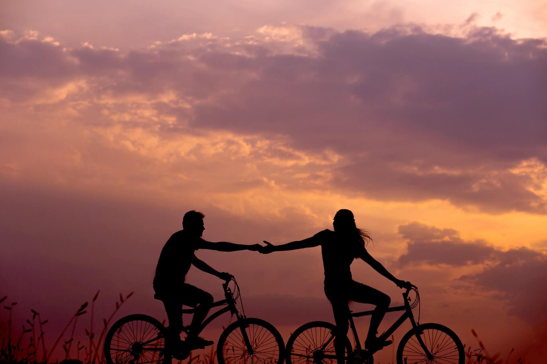 Mann und Frau auf Rädern reichen sich die Hand